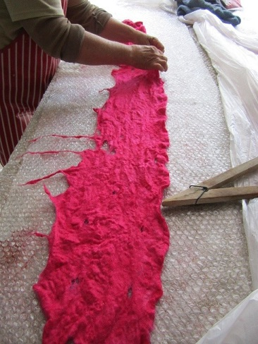 """ \""Stretch the felt scarf into shape and re-establish any holes\"""""