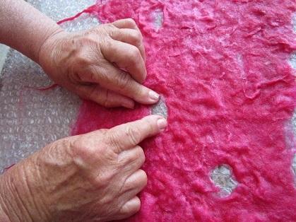 Re-establish any holes and fringe on the felt scarf