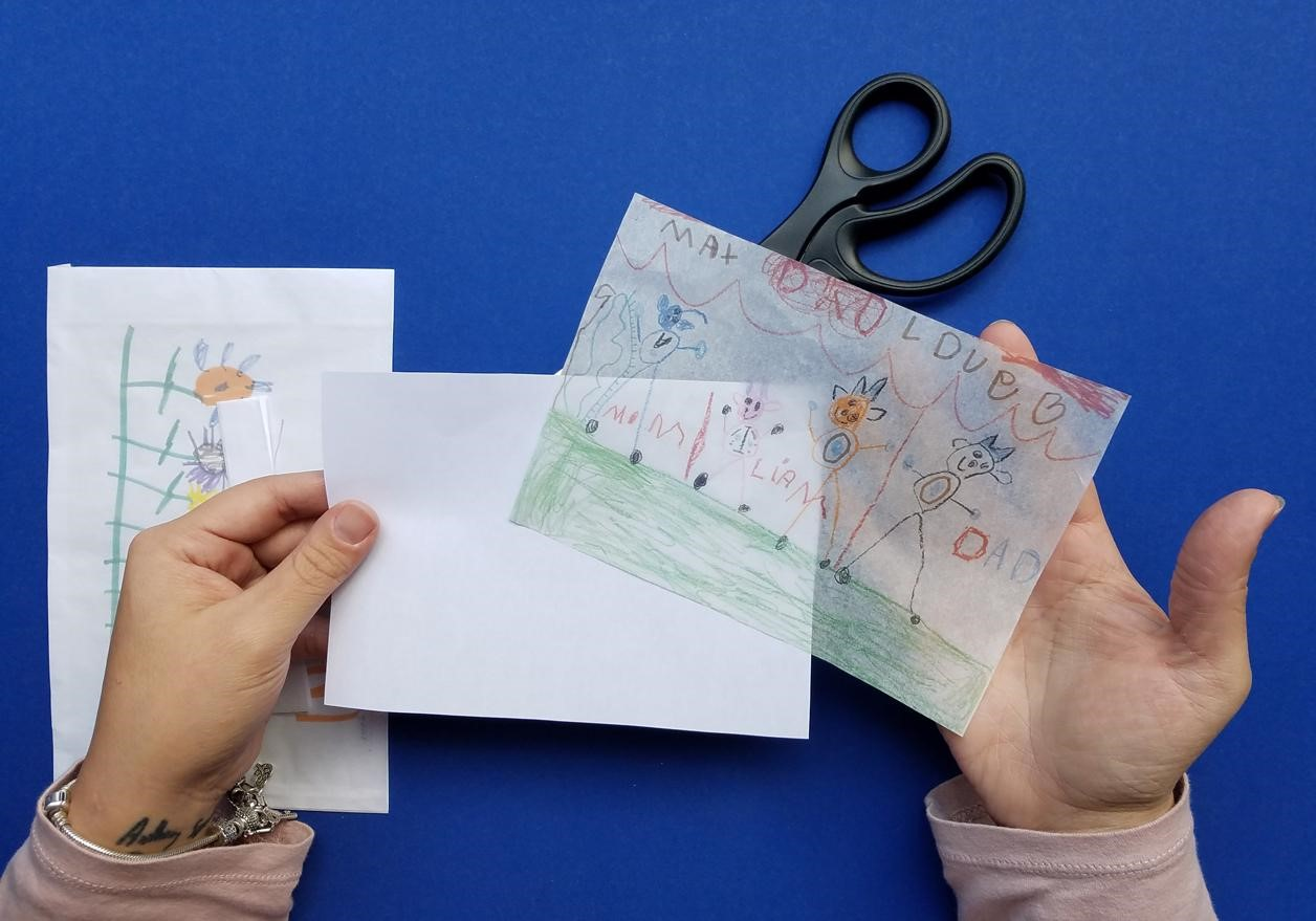 You won't even have to untape the tissue paper. Cut around the edges of your photo and it will slide off easily.